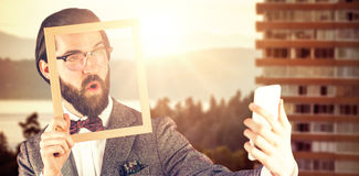 Composite image of businessman taking selfie while holding frame stock photography