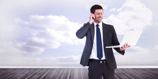 Composite image of businessman talking on phone holding laptop Royalty Free Stock Photo