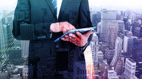 Composite image of businessman touching his tablet pc. Businessman touching his tablet pc  against high angle view of city Royalty Free Stock Images