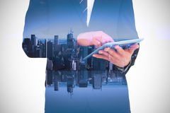 Composite image of businessman touching his tablet pc Stock Photography