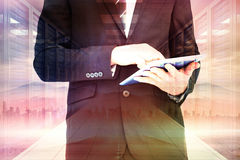 Composite image of businessman touching his tablet pc. Businessman touching his tablet pc  against sun shining over road and city Royalty Free Stock Image