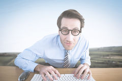 Composite image of businessman typing on his keyboard wearing glasses Royalty Free Stock Photo