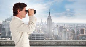 Composite image of businessman using binoculars Stock Photos