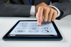 Composite image of businessman using digital tablet. Businessman using digital tablet against telephone apps icons Stock Photos
