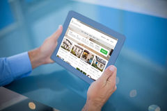Composite image of businessman using his tablet Stock Photography