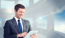 Composite image of businessman using his tablet pc Royalty Free Stock Photography