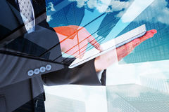 Composite image of businessman using his tablet pc Stock Images