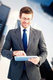 Composite image of businessman using his tablet pc Royalty Free Stock Photos