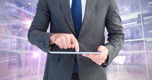 Composite image of businessman using his tablet pc Stock Image