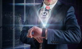 Composite image of businessman using hologram watch Royalty Free Stock Photos