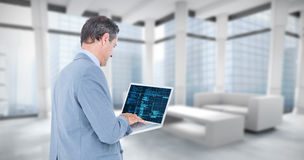 Composite image of businessman using laptop. Businessman using laptop against modern room overlooking city Royalty Free Stock Image