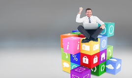 Composite image of businessman using laptop and cheering Stock Photography