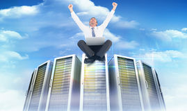 Composite image of businessman using laptop and cheering Royalty Free Stock Photo