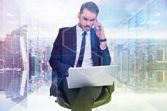 Composite image of businessman using laptop while phoning Royalty Free Stock Image