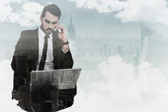 Composite image of businessman using laptop while phoning Stock Photo