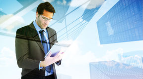 Composite image of businessman using a tablet computer Royalty Free Stock Photo