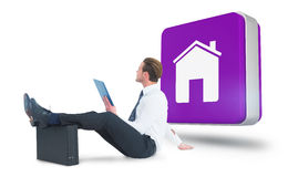 Composite image of businessman using tablet with feet up on briefcase Royalty Free Stock Photos