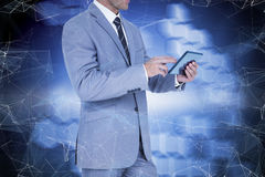 Composite image of businessman using tablet pc. Businessman using tablet pc against technological background with hexagons stock image