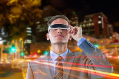 Composite image of businessman using virtual reality glasses against white background. Businessman using virtual reality glasses against white background against Stock Images