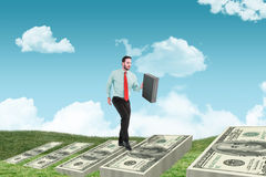 Composite image of businessman walking while holding briefcase Stock Photos