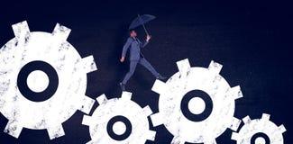 Composite image of businessman walking and holding umbrella Stock Photo