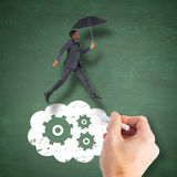 Composite image of businessman walking and holding umbrella Royalty Free Stock Images