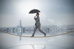Composite image of businessman walking and holding umbrella on tightrope Royalty Free Stock Photography
