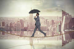 Composite image of businessman walking on tightrope and holding umbrella Stock Image