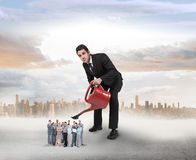 Composite image of businessman watering tiny business team Royalty Free Stock Photography