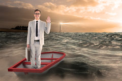 Composite image of businessman waving in boat Stock Photo