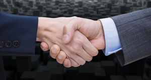 Composite image of businessman and woman doing handshake. Businessman and woman doing handshake against computer graphic image of black blocks Royalty Free Stock Photo