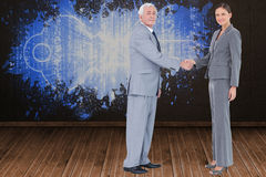 Composite image of businessman and woman shaking hands Royalty Free Stock Images