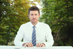 Composite image of businessman working at his desk Stock Photography
