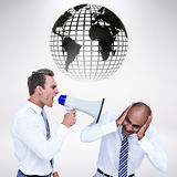 Composite image of businessman yelling with a megaphone at his colleague Stock Image