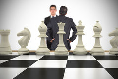 Composite image of businessmen and chess pieces Stock Photos