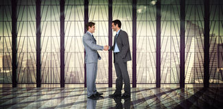 Composite image of businessmen shaking hands Stock Photos