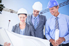 Composite image of businessmen and a woman with hard hats and holding blueprint Royalty Free Stock Images
