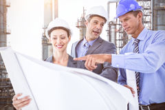 Composite image of businessmen and a woman with hard hats and holding blueprint Stock Photo