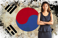 Composite image of businesswoman with crossed arms. Businesswoman with crossed arms against korea republic flag in grunge effect Stock Photography