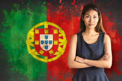 Composite image of businesswoman with crossed arms. Businesswoman with crossed arms against portugal flag in grunge effect stock photo