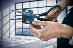 Composite image of businesswoman cutting credit card with scissors. Businesswoman cutting credit card with scissors against room with large windows showing city royalty free stock image