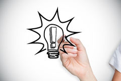 Composite image of businesswoman drawing light bulb Royalty Free Stock Photography