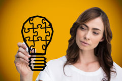 Composite image of businesswoman drawing light bulb Stock Photography
