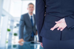 Composite image of businesswoman with fingers crossed behind her back Royalty Free Stock Photos