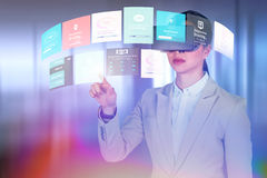 Composite image of businesswoman gesturing while wearing virtual video glasses stock image