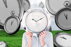 Composite image of businesswoman hiding face with clock Royalty Free Stock Image