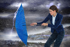 Composite image of businesswoman holding blue umbrella royalty free stock photos