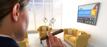 Composite image of businesswoman holding cigar. Businesswoman holding cigar against yellow sofas in living room at modern house Royalty Free Stock Photography