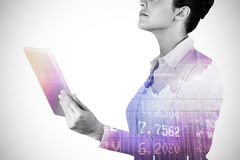 Composite image of businesswoman holding digital tablet 3d. Businesswoman holding digital tablet against stocks and shares 3d Stock Photos