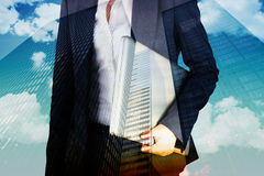 Composite image of businesswoman holding laptop. Businesswoman holding laptop against low angle view of skyscrapers royalty free stock images